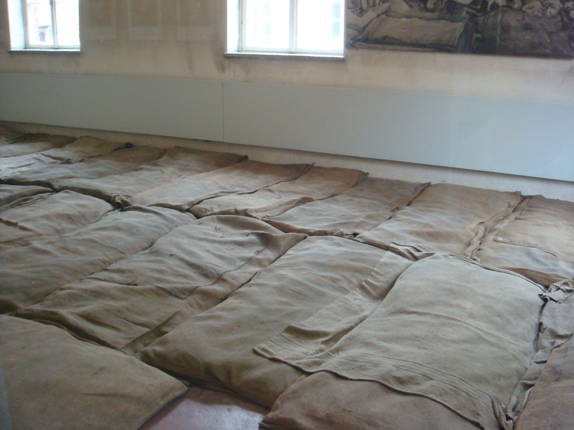 A bunkroom where Polish political prisoners first slept.  Crowded and unheated, but with a semblance of a mattress.